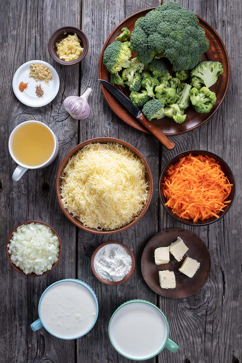 ingredients of broccoli cheese soup on a wood background