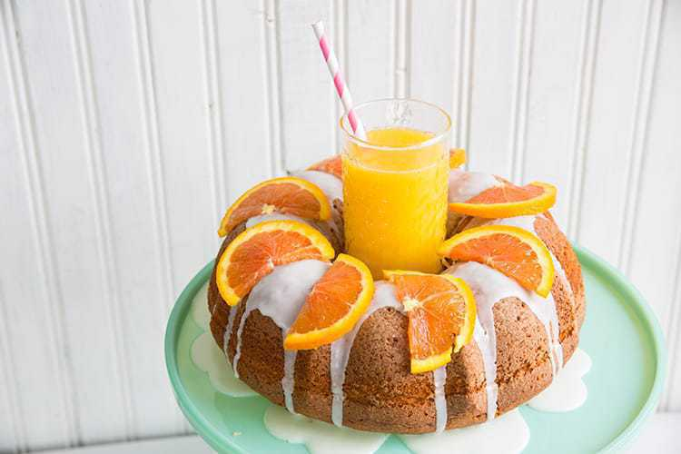 Harvey Wallbanger Cake with Boozy Glaze and slices of oranges on top, a glass of orange juice at the center of bundt cake