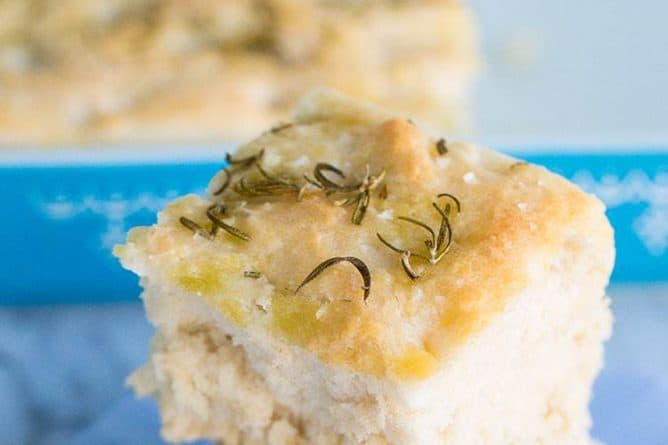 close up slices of Focaccia Bread on blue plate and baking pan