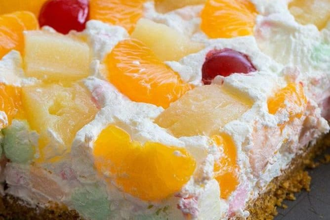 Close up of Ambrosia Salad Squares Topped with Mandarin Slices, Pineapple Chunks and Maraschino Cherries