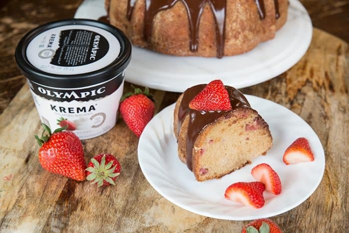 Strawberry Yogurt Bundt Cake topped with chocolate satin glaze and fresh strawberries and a Cup of Olympic Krema yogurt