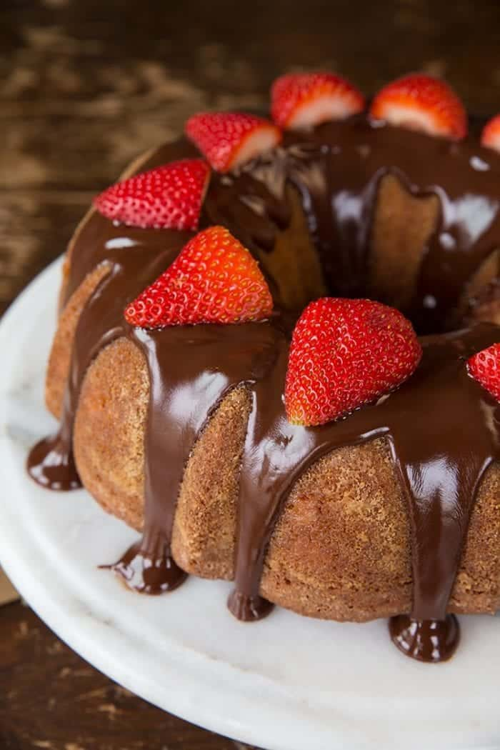 Close up of Strawberry Yogurt Bundt Cake topped with chocolate satin glaze and fresh strawberries