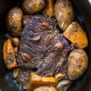 beef roast on a Dutch oven with vegetables around, garlic and thyme on top