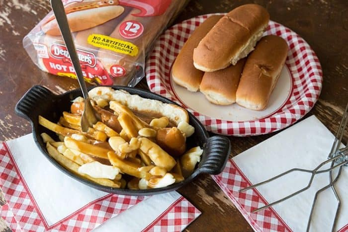 How to Make Poutine Hot Dogs! This crazy Canadian treat uses melty cheese curds and gravy on top of a hot dog! SO DELICIOUS!