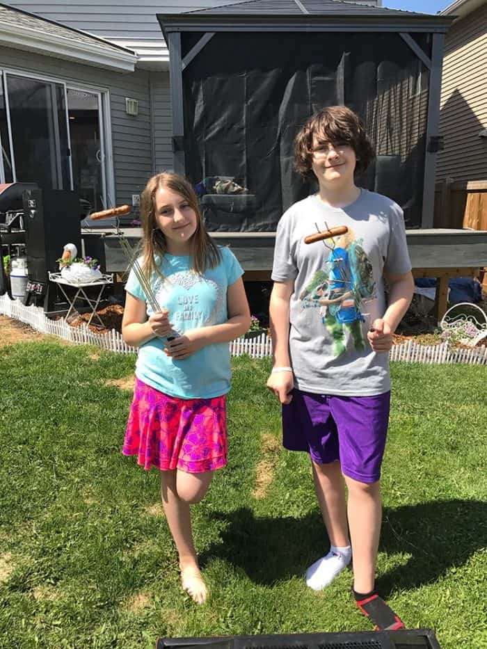 kids holding cooked hot dogs each