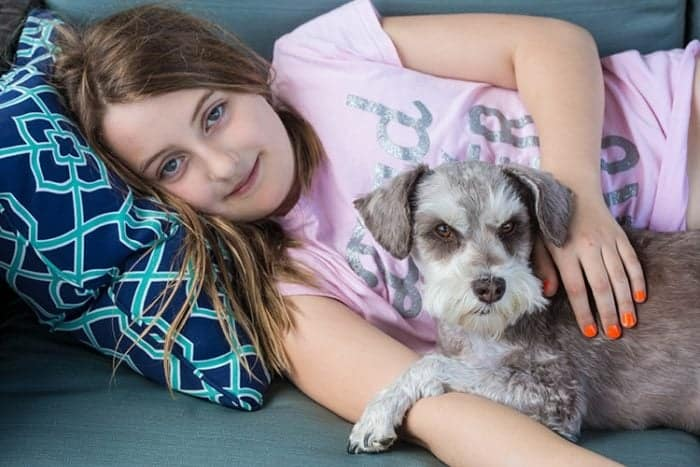 girl in pink shirt laying on coach with her dog