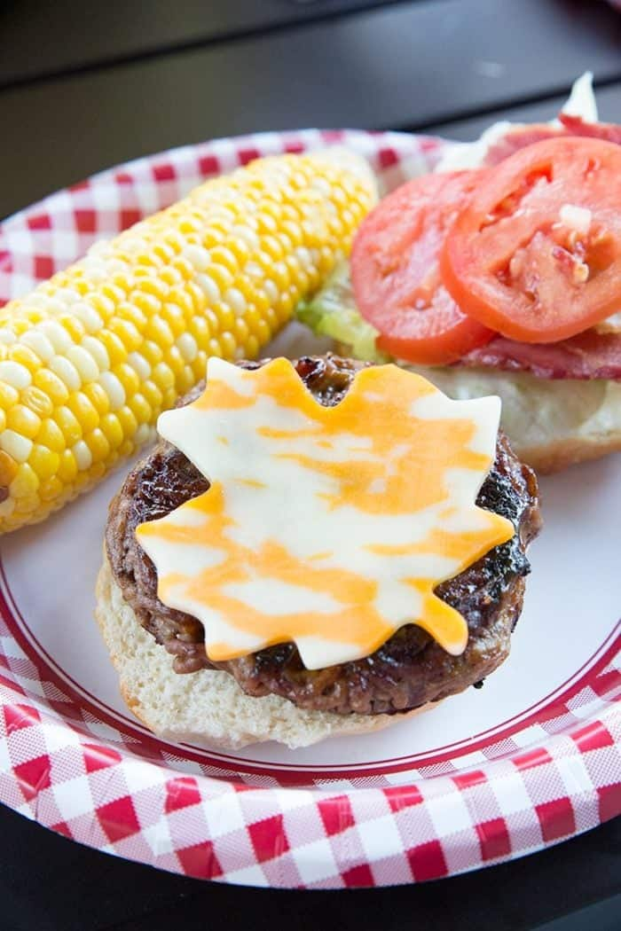 a plate with corn and burgers with slices of tomatoes