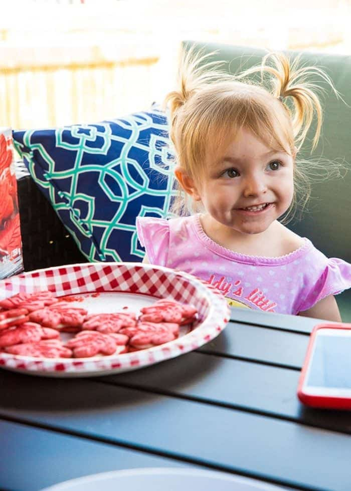 a plate with maple cookies in front of little girl in pink dress