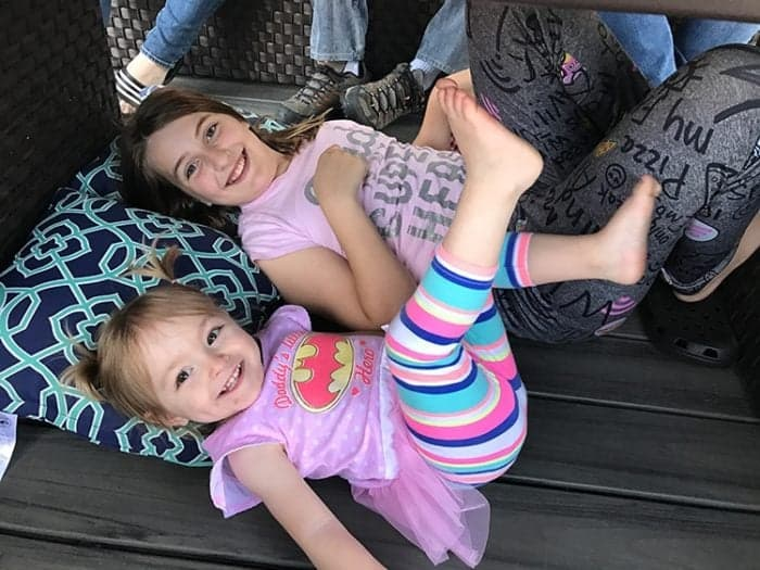 two little girls laying with feet up