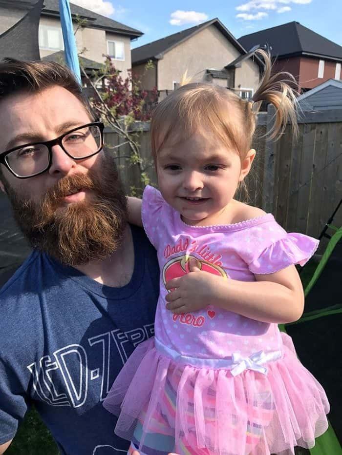 man wearing eyeglasses carrying a little girl in pink dress