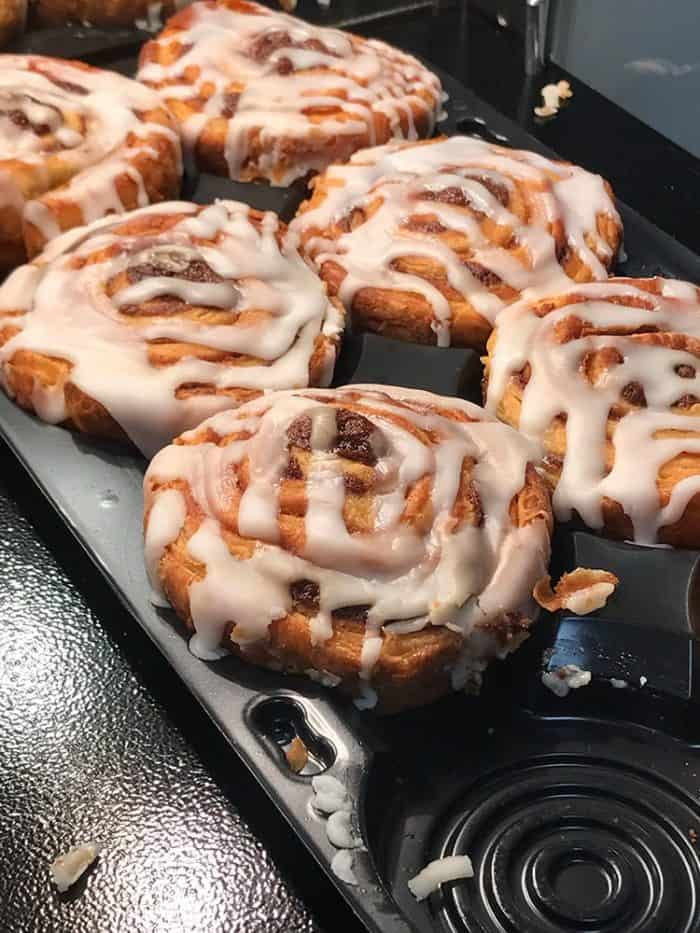 close up of cinnamon buns with white glaze