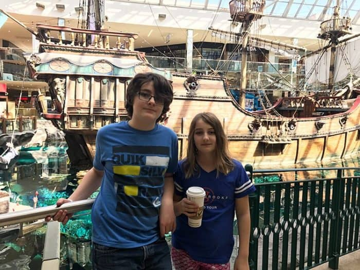 two kids standing near the grills with a large ship in their background