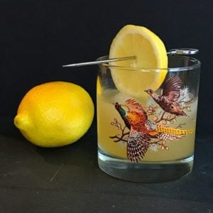 Fresh lemon fruit beside a vintage glass with Boating Punch Cocktail garnish with a slice of lemon