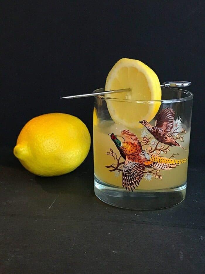 Fresh lemon fruit beside a vintage glass with Boating Punch Cocktail garnish with a slice of lemon