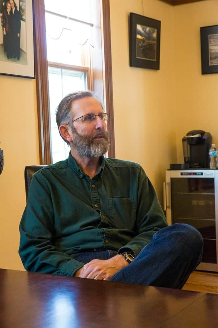 man wearing eye glasses, long sleeves dark green polo shirt, sitting near the table