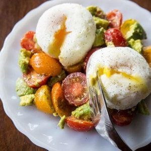 Breakfast Salad in white plate with Poach eggs on top