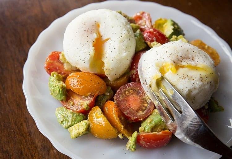 Pesto Tomato, Egg & Avocado Breakfast Salad in a white plate
