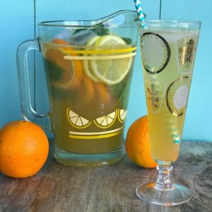 A pitcher and a glass of Sparkling Bourbon Lemonade with slices of oranges