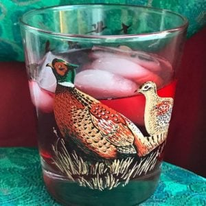 vintage bird glass with oppenheim cocktail and ice on red and green background