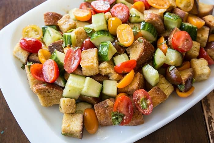 A plate of Panzanella Salad with cherry tomatoes, cucumbers and a basil