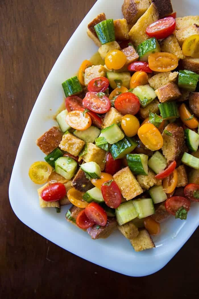 A plate of Summer Panzanella Salad with cherry tomatoes, cucumbers and a basil