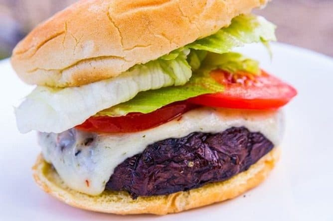 close up of Homemade Portobello Mushroom Burger in white plate with slices of tomatoes and lettuce