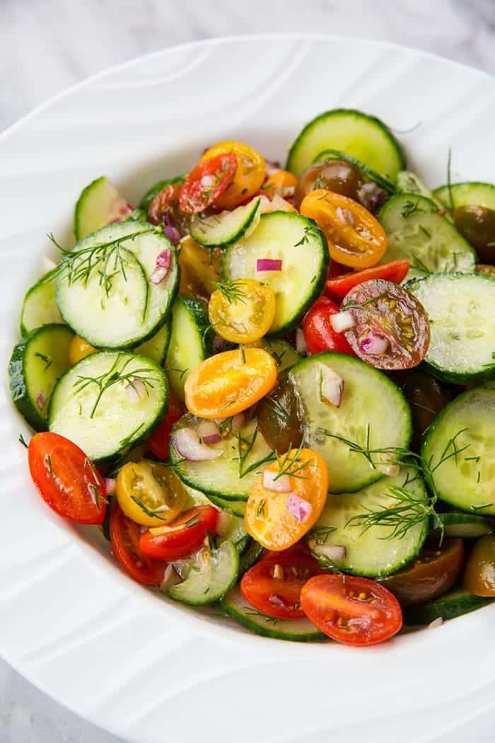 Cucumber Salad with Tomato and Dill in a large white serving bowl