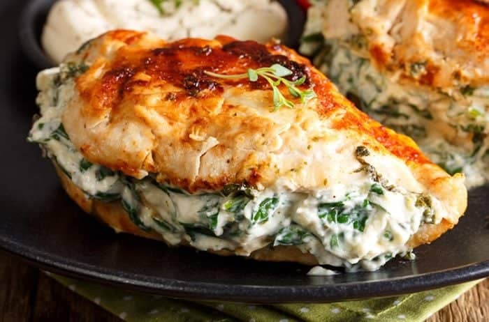 Pan Fried Spinach & Cream Cheese Stuffed Chicken Breasts in a black plate