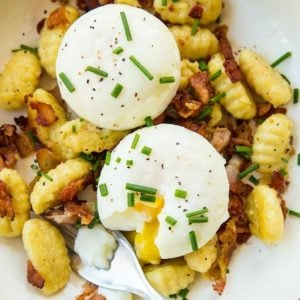 top down shot of Gnocchi Breakfast Skillet with bacon, green onions and top with eggs