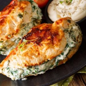 close up Pan Fried Stuffed Chicken Breasts with Spinach & Cream Cheese in a black serving plate