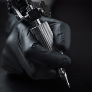 holding a tattooing equipment hands with black glove on dark background
