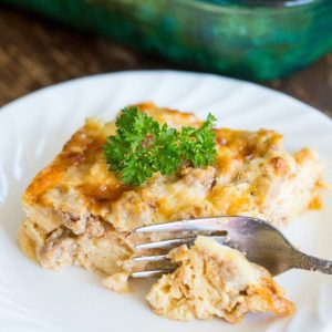 a slice of Breakfast Casserole in a white plate, Pyrex baking pan on background