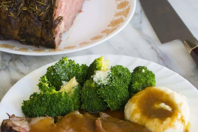 Prime Rib roast plated with broccoli and mashed potatoes topped with gravy. A knife and a plate with whole prime rib roast on background