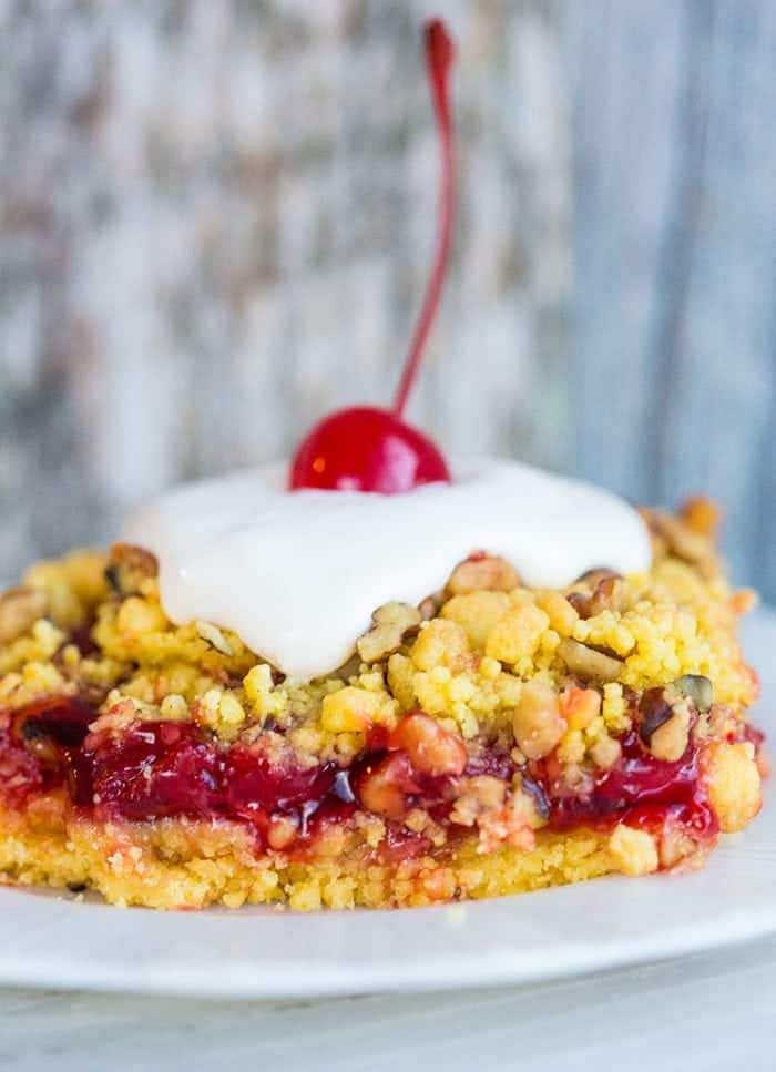 Close up of a Lemon Cherry Crunch Cake on a white plate