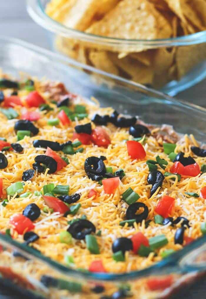Pyrex baking dish with Tex-Mex 7 Layer Dip topped with tomatoes, green onions, shredded cheese and black olives