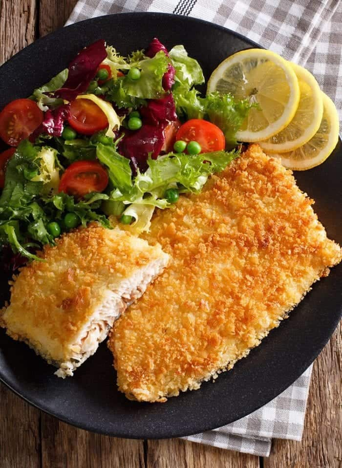 black plate loaded with Air Fryer Fish Fillets garnish with lemon wedges and vegetables