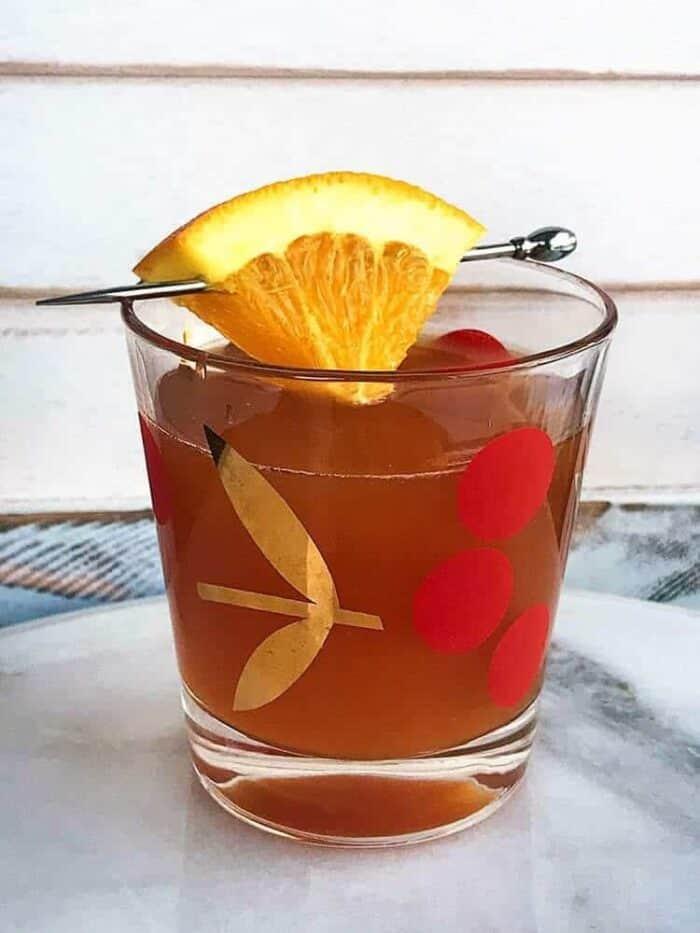 Alabama Slammer Cocktail in Cherries vintage glass garnish with a small slice of orange