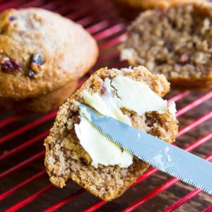 Adding Spread to Half Sliced Oat Bran Muffins on Red Cooling Rack