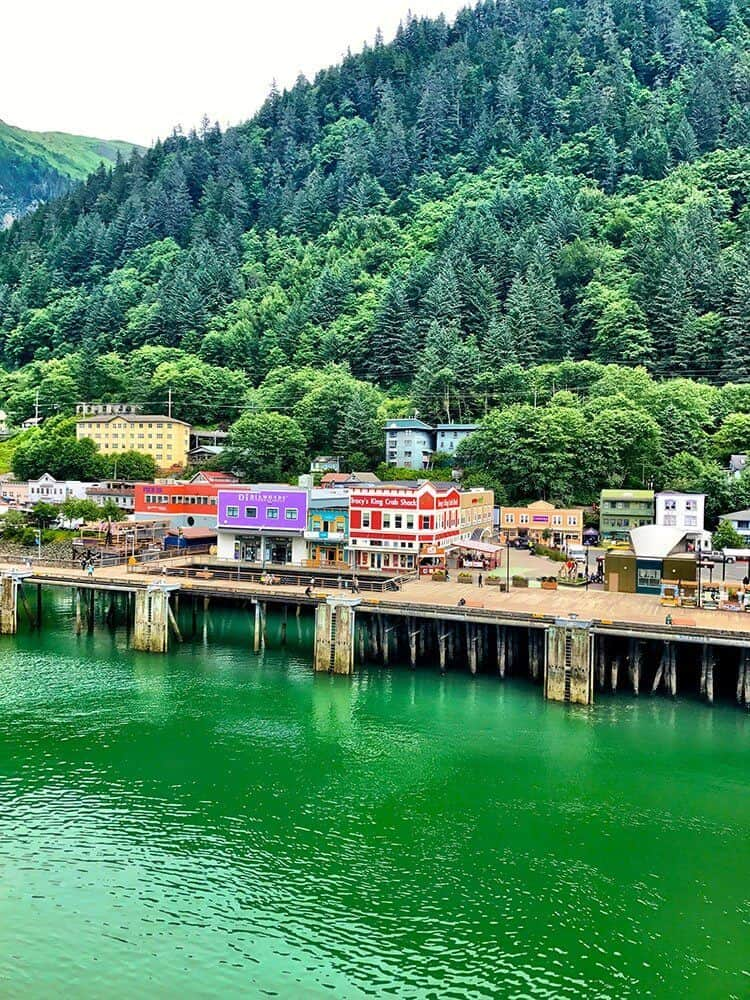 Juneau port with a view of colorful establishments and high pine trees