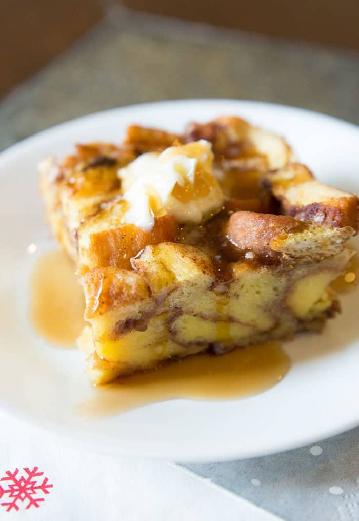 Leftover Cinnamon Rolls French Toast Casserole with Syrup in a White plate