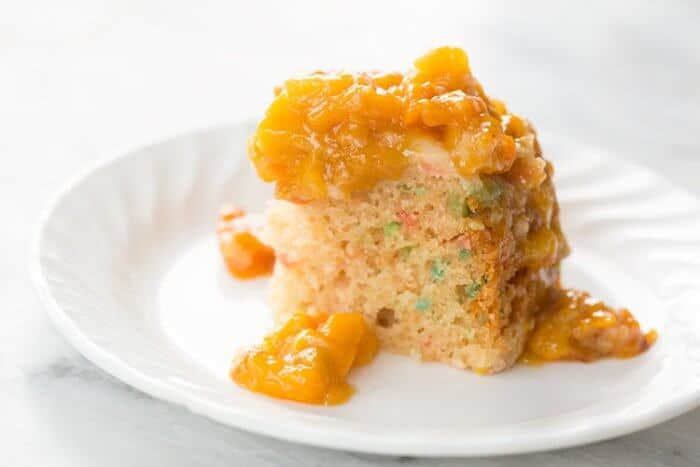 Slice of Peachy Slow Cooker Confetti Cake in a White Plate Topped with Peach Topping