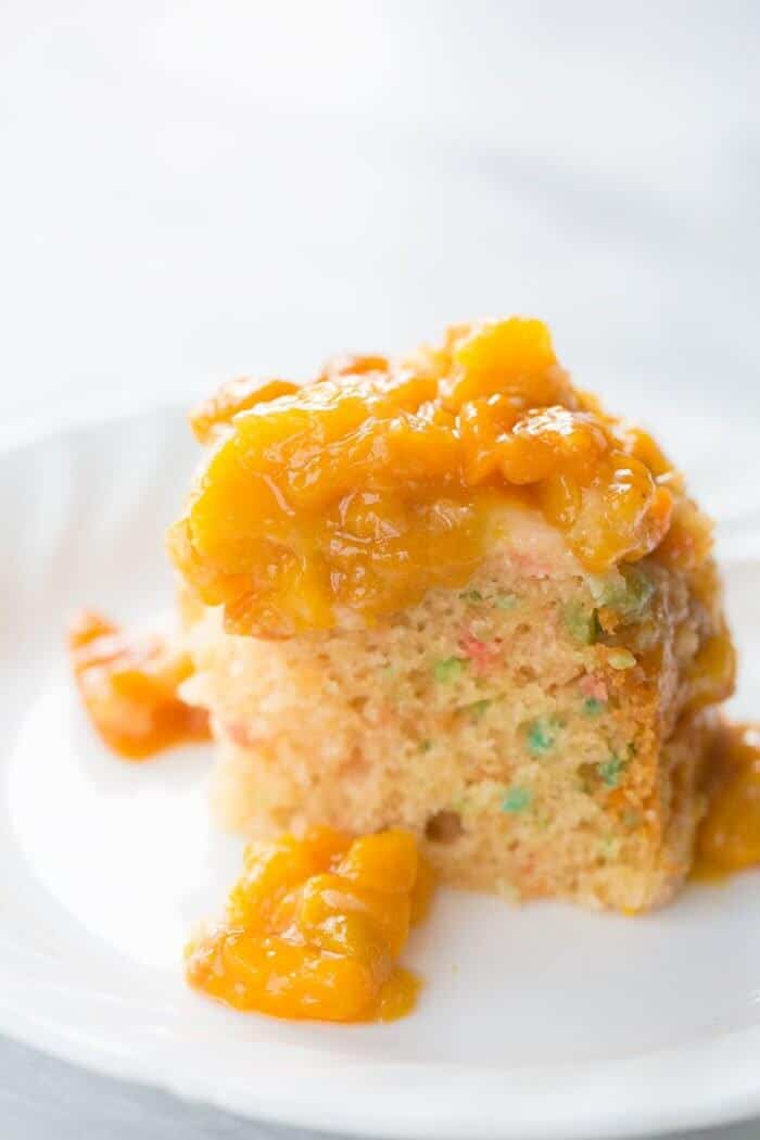 Close up Slice of Confetti Cake in a White Plate Topped with Peach Topping