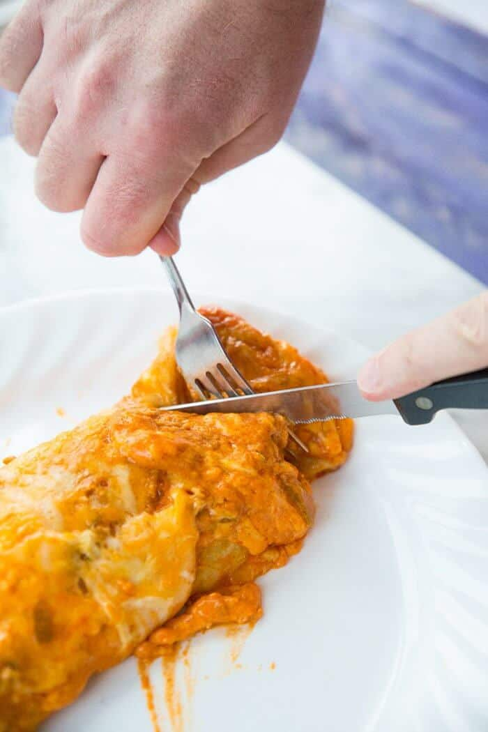 Slicing the Sour Cream Steak Enchiladas in white plate using a fork and knife