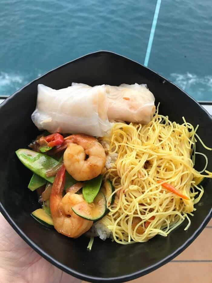 black plate with with noodles, vegetables and shrimp