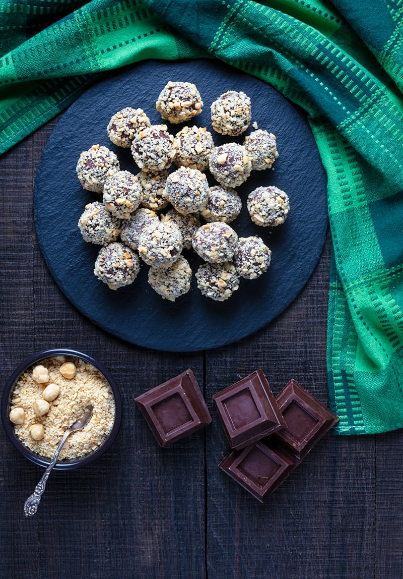 Hazelnut Truffles on a large plate, green tablecloth chocolate squares and finely chopped roasted hazelnuts on its side