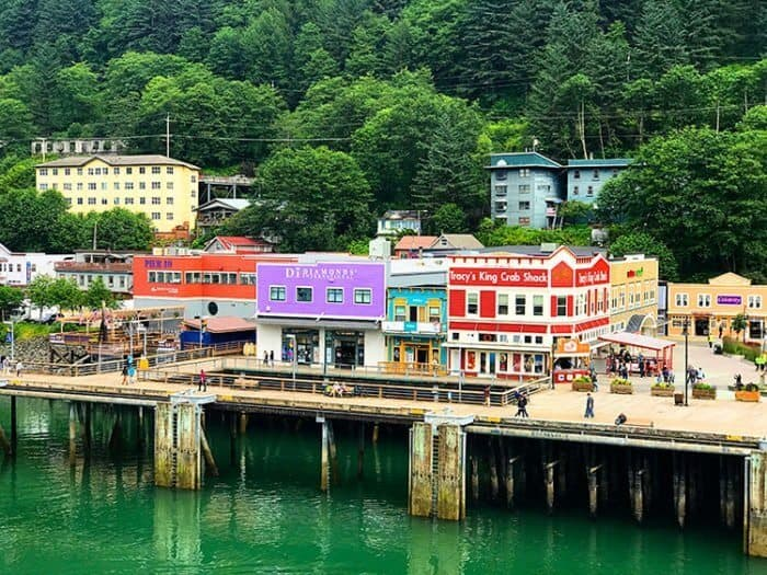 Juneau port with colorful establishments and tall trees background