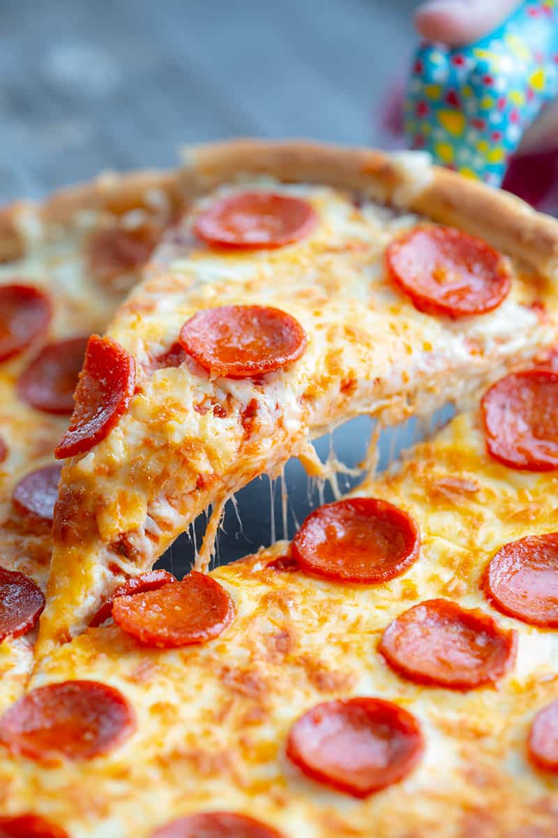 close up slice of simple pizza crust stuffed with cheese and pepperoni