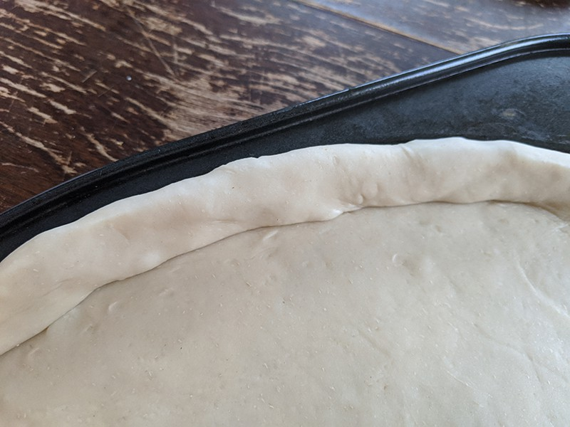simple pizza dough in a pizza pan