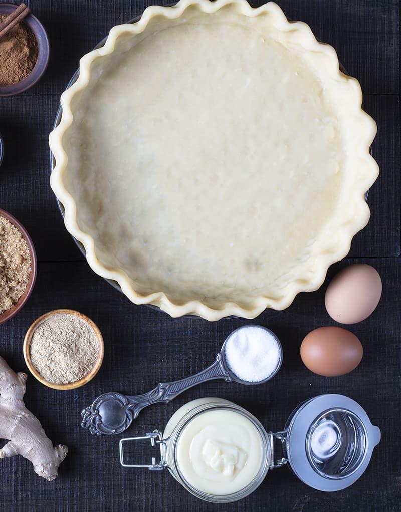unbaked pie crust in a pie pan and Pumpkin Pie ingredients around it