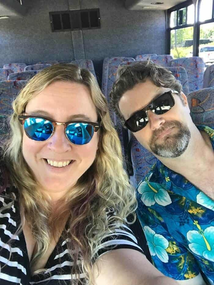 Selfie on shuttle going to the pier, woman wearing stripe black blouse and man wearing blue floral polo shirt